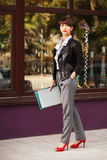 Fashion business woman in leather jacket walking in city street Royalty Free Stock Photos