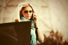 Fashion business woman in sunglasses calling on cell phone next to car Stock Images