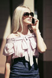 Fashion business woman in sunglasses calling on mobile phone. Fashion blond business woman in sunglasses calling on mobile phone Stock Photo