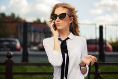 Fashion business woman in sunglasses calling on mobile phone Royalty Free Stock Images