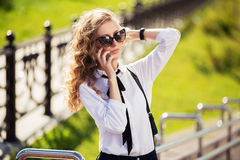 Fashion business woman in sunglasses calling on mobile phone Stock Photography