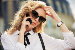 Fashion business woman in sunglasses calling on mobile phone Stock Images