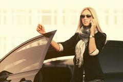 Fashion business woman in sunglasses talking on cell phone outside her car Royalty Free Stock Images