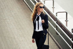Fashion business woman in sunglasses walking on city street Royalty Free Stock Images