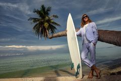Fashion businessman with surfboard on the beach royalty free stock image