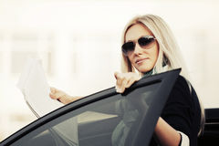 Fashion businesswoman with financial papers by car Stock Photo
