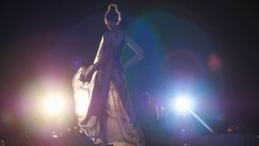 Fashion catwalk, model girl in chiffon dress and stylish shoes goes down podium in bright spotlights. At night stock video footage