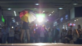 Fashion catwalk, model with umbrella posing and walk at podium in lighting on background blurred audience