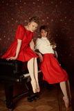 Fashion caucasian ballerinas sitting on the piano and laughing Stock Photos