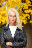 Fashion caucasian blonde woman in black jacket and white sweater royalty free stock images
