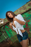 Fashion Caucasian model posing outdoor in front of an old boat. Brunette with white shirt and denim shorts near an old boat. Amazing attractive woman royalty free stock photos