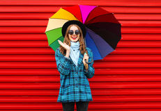 Fashion cheerful smiling woman holds colorful umbrella wearing black hat checkered coat jacket over red Royalty Free Stock Image