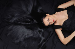 Fashion chic woman with long bright black hair and silk shiny sk Stock Photos