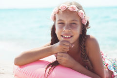 Fashion child at the beach. 9 years old girl dressed in fashion floral swimsuit and denim shorts posing with inflatable ring at the beach in sunlight Royalty Free Stock Photography