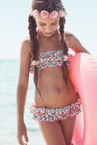 Fashion child at the beach. 9 years old girl dressed in fashion floral swimsuit posing with inflatable ring at the beach in sunlight Stock Photography