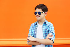 Fashion child boy wearing a sunglasses and shirt in city. Against colorful orange background royalty free stock images