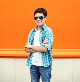 Fashion child boy wearing a sunglasses and shirt in city Stock Image