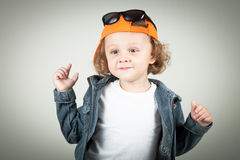 Fashion child. Happy boy model. Stylish little boy in baseball.  Handsome  kid  in the jeans jacket Royalty Free Stock Image