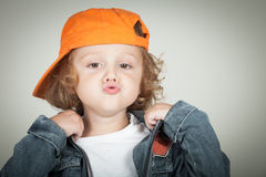 Fashion child. Happy boy model. Stylish little boy in baseball.  Handsome  kid  in the jeans jacket Royalty Free Stock Photography