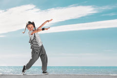 Fashion child pointing on copy space over sky background. Royalty Free Stock Photo