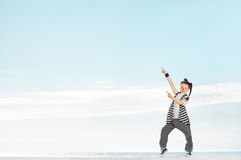 Fashion child pointing on copy space over sky background. Royalty Free Stock Image