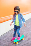 Fashion child on skateboard wearing a sunglasses and checkered shirt Royalty Free Stock Image