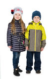 Fashion children in the winter jackets. Two fashion children in the winter jackets  are standing together against the white background Royalty Free Stock Photos