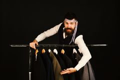 Fashion choice concept. Designer leans on clothes hangers. Man with beard in vest. By clothes rack. Tailor with cheerful face and measuring tape tied around stock photography