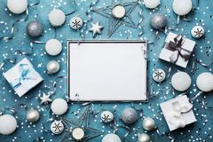 Fashion christmas background. Silver frame with xmas decoration, gift box and sequins. Party mockup or festive invitation.