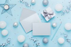 Fashion christmas mockup for greeting. Envelope, paper card, gift box and decoration on blue table top view. Flat lay style. Stock Photo
