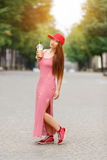 Fashion city portrait of stylish hipster woman with milk shake, red striped dress, red cap and sneakers, makeup, long stock photos