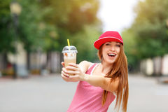 Fashion city portrait of stylish hipster woman with milk shake, red striped dress, red cap and sneakers, makeup, long royalty free stock photos