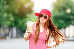 Fashion city portrait of stylish hipster woman with milk shake, red striped dress, red cap and sneakers, makeup, long Royalty Free Stock Image