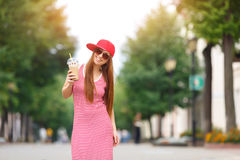 Fashion city portrait of stylish hipster woman with milk shake, red striped dress, red cap and sneakers, makeup royalty free stock images