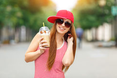 Fashion city portrait of stylish hipster woman with milk shake, red striped dress, red cap and sneakers, makeup royalty free stock photo