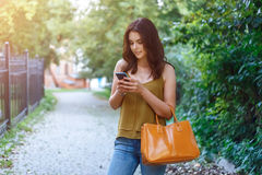 Fashion city portrait of stylish hipster woman with mobile phone, makeup, long brunette hairs, enjoy vacation in Europe stock photos
