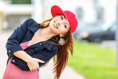 Fashion city portrait of stylish hipster woman, red striped dress, red cap and sneakers, makeup, sunglasses, long royalty free stock images