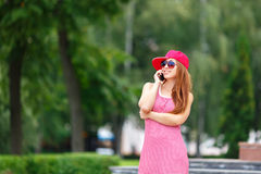 Fashion city portrait of stylish hipster woman talking mobile phone, red striped dress, red cap and sneakers, makeup Royalty Free Stock Photography