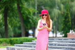 Fashion city portrait of stylish hipster woman talking mobile phone, red striped dress, red cap and sneakers, makeup Stock Photo