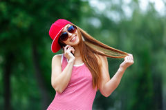 Fashion city portrait of stylish hipster woman talking mobile phone, red striped dress, red cap and sneakers, makeup royalty free stock image