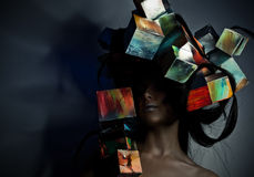 Fashion close-up portrait of beautiful young girl with cubes on head. Conceptual photo. Stock Photos