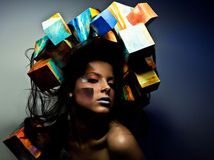 Fashion close-up portrait of beautiful young girl with cubes on head. Conceptual photo. Stock Photography