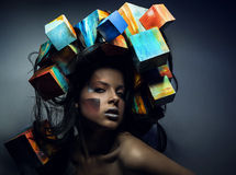 Fashion close-up portrait of beautiful young girl with cubes on head. Royalty Free Stock Images