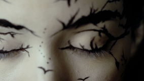 Fashion close-up slow motion portrait of model female with a amazing creative make-up. Painted muah silhouettes of trees and birds. Calm face, halloween. Dark stock video