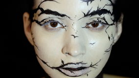 Fashion close-up slow motion portrait of model female with a amazing creative make-up. Painted muah silhouettes of trees and birds. Calm face, halloween. Dark stock video footage