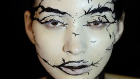 Fashion close-up slow motion portrait of model female with a amazing creative make-up. Painted muah silhouettes of trees and birds. Calm face, halloween. Dark stock footage