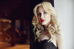 Fashion closeup of a beautiful blond woman in sexy tight black d Stock Photos