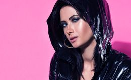 Fashion closeup portrait of young beautiful woman with expressive eyes. Stylish glossy black cloak with a hood. Youth appearance. Bright pink background stock photo