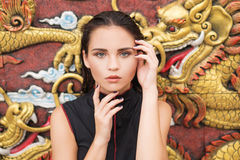Fashion closeup of young brunette woman over golden dragon on the wall Royalty Free Stock Photo