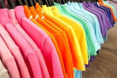 Fashion clothes on clothing rack - bright colorful closet. Close-up of rainbow color choice of trendy female wear. On hangers in store closet or spring cleaning royalty free stock photography